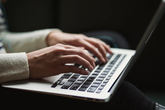 A writer typing on their laptop