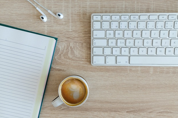 A notebook, cup of coffee, and a keyboard